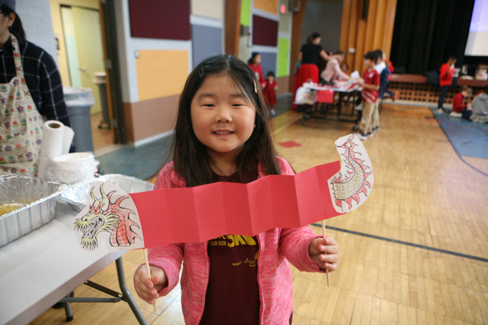 young girl showing the paper dragon she made