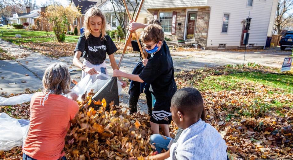 Kids playing in a yard raking leaves